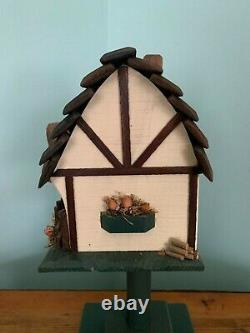 Handcrafted birdhouse cottage with wind-up music box and handmade stand